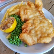 COD & CHIPS topped with a wedge of Lemon and served with fries, garden peas and tartare sauce